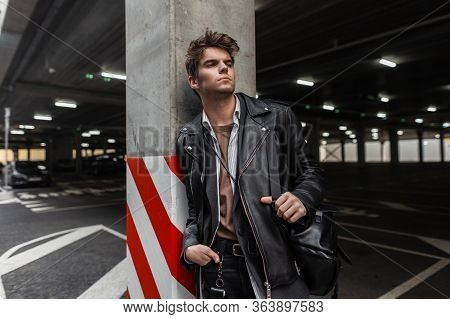 Fashionable Urban Young Hipster Man With A Stylish Hairstyle In Trendy Oversized Leather Jacket In A