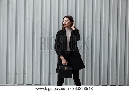 Stylish Cute Young Woman With Brown Long Hair In Seasonal Trendy Black Coat With Fashion Leather Bag