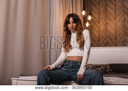 Young Beautiful Woman With Long Red Hair In A Stylish T-shirt In Fashionable Blue Jeans Sitting On A