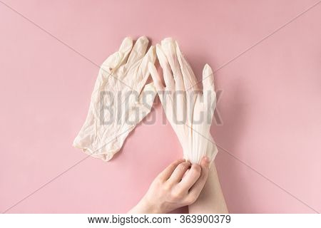 Female Hand Puts On White Disposable Rubber Glove On Pink Background Top View. Viruses And Bacteria