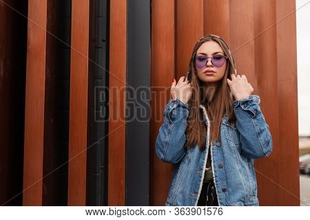 Modern Attractive Young Woman In Stylish Blue Denim Jacket In Military Hoodie With Fashionable Purpl