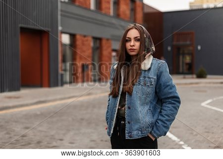 Young Fashionable Pretty Urban Woman In Youth Blue Denim Jacket Is Poses Near Building In The City.