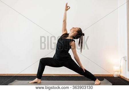 Young Woman Trainer Doing Yoga And Stretching. Professional Girl Coach Keeps Balance.