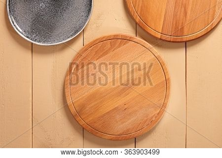 Wooden pizza boards and gray ceramic plate top view. Restaurant tableware, pizzeria utensil, serving items. Kitchen stuff, circular boards, cutting desks and empty dish on wooden table