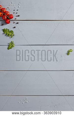Cherry tomatoes and spices on wooden table top view. Vegetables and greenery leaves, black peppercorns and salt on wooden boards. Veggies and flavoring, rustic style backdrop  decoration
