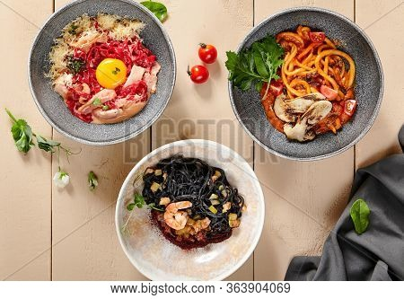 Noodles in ceramic bowls top view. Cooked flour products with sauces, spaghetti with meat, seafood and vegetables. Served pasta, restaurant meals on wooden table, rustic style serving