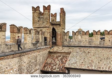Sirmione, Italy, October 01, 2015 : Tourists Walk On The Walls Of The Castello Scaligero Fortress In
