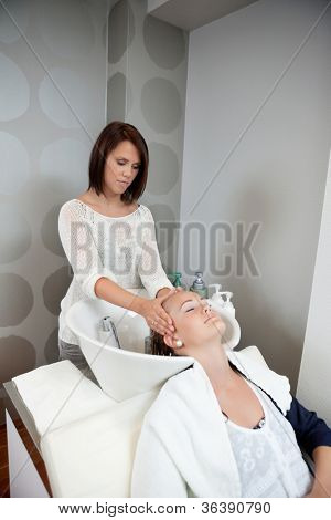Young woman getting a massage while having hair wash at salon by hairdresser