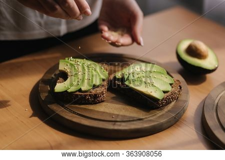 Woman Making Vegan Sandwich Using Rye Toasted Bread Avocado And Sesame Seeds. Woman Sprinkle With Se