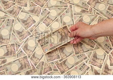 Hand Holding A 10,000 Yen Banknote - Background With Several 10,000 Yen Banknotes (front). Japanese
