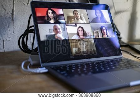 People Doing A Virtual Meeting Online.  Laptop On Work From Home Desk.  Coworkers In A Team Meeting