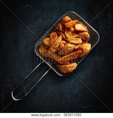 Top View Of Tasty Golden Potatoes In Metal Basket On Black Background
