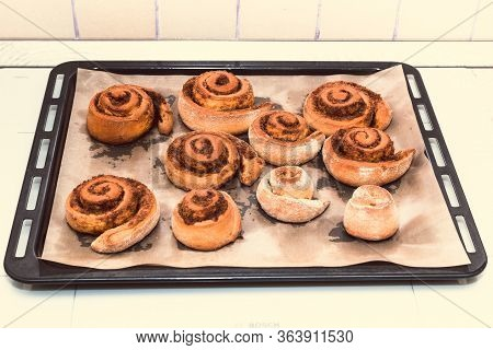 Rolled Bread Rolls With Sugar And Cinnamon On A Metal Baking Sheet Baked In The Home Kitchen