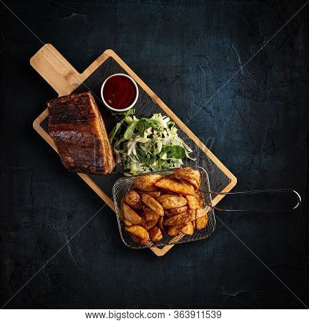 Delicious Barbecued Ribs Served With Golden Potatoes And Bbq Sauce On Dark Background