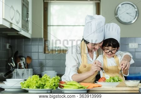 Cooking Family. Chef Kid Boy And Mother Making And Leaning Fresh Vegetables Salad For Healthy Eat An