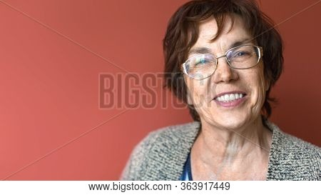 Close Up Portrait Of A Happy Smiling Elder Woman Over Dark Red Background. Helathy Lifestyle And Den