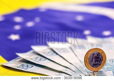 One Real Coin With Brazil Money Banknotes On Background With National Flag. Concept Of Brazil Econom
