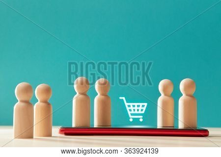 Wooden Person Figures On Smartphone And Trolley Sign. E-store, E-commerce. Online Shopping Via Mobil