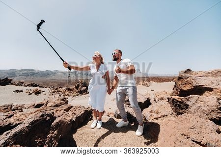 A Stylish Woman Takes A Selfie In The Crater Of The Teide Volcano. Desert Landscape In Tenerife. Tei