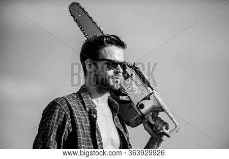 Get Stylish Haircut. Barbershop Concept. Masculinity Concept. Handsome Man With Chainsaw Blue Sky Ba