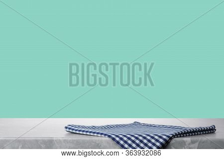 Folded Kitchen Towel On Grey Table Against Mint Background. Space For Design
