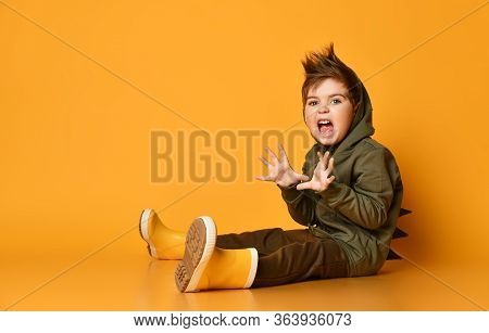 Playful Little Brunet Boy In Brown Dino Hoodie Sits On The Floor, Growling, Scaring, Holding Hands L