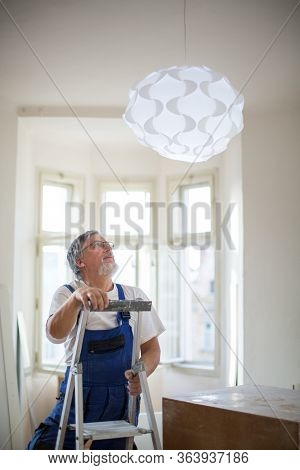DIY, repair, building and home concept - Senior landlord hanging a new light in a rental appartement (shallow DOF; color toned image)