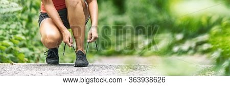 Road to Fitness healthy girl getting ready to run tying shoe laces outside lacing running shoes in summer park banner panorama. Health active lifestyle woman exercising outdoors.