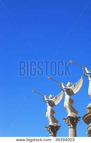 The statues of winged troubadours against the blue sky decorated capitals of the columns.