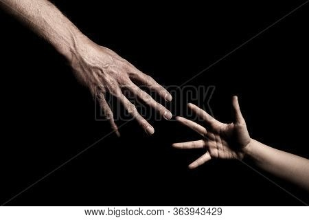 Hands Reaching Out To Each Other On Dark Black Background