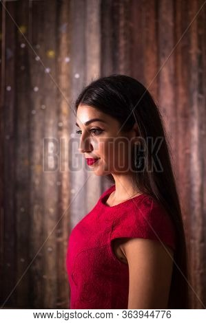 Portrait Of A Muslim Girl In Red Dress And With Red Lipstick. Side Shot Of Middle Eastern Woman With