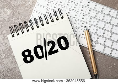 Pareto Principle Concept. Notebook With 80/20 Rule Representation, Pen And Keyboard On Grey Backgrou