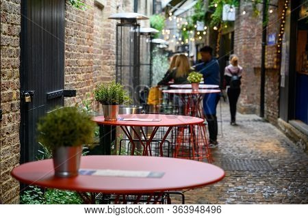 London - September 30, 2019: A Row Of Tables On A Cobbled Street In An Outdoor Dining Area Of Camden