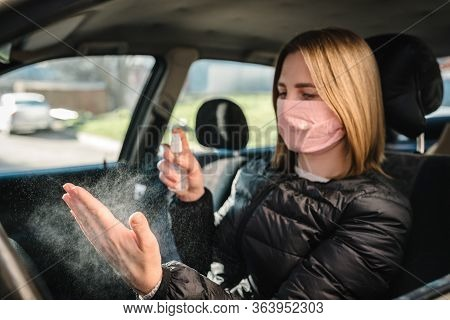 Spraying Antibacterial Sanitizer Spray On Hand In Car, Infection Control Concept. Sanitizer To Preve