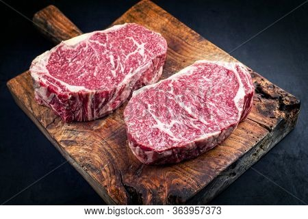 Raw dry aged wagyu entrecote beef steak roast as closeup on a rustic wooden cutting board