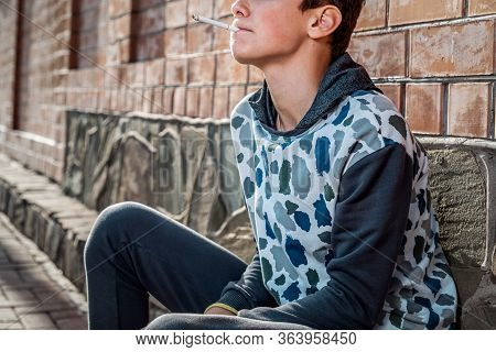 Smoking. Close Up Portrait Of A Teenage Boy Smoking A Cigarette With A Confident Look. Brick Wall In