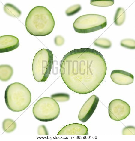 Cucumber Slices Flying In Air On White Background. Set Of Falling Cut Fresh Cucumber Close Up. Green