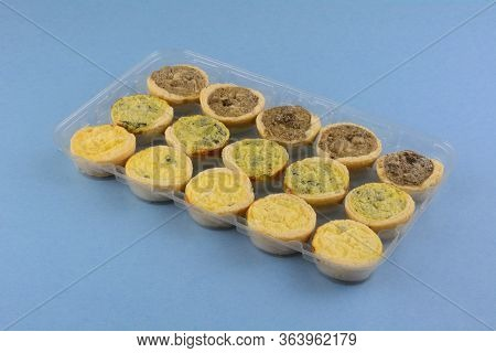 Frozen Mini Spinach Florentine, Cheese And Mushroom Quiches In Plastic Packaging On Blue Background