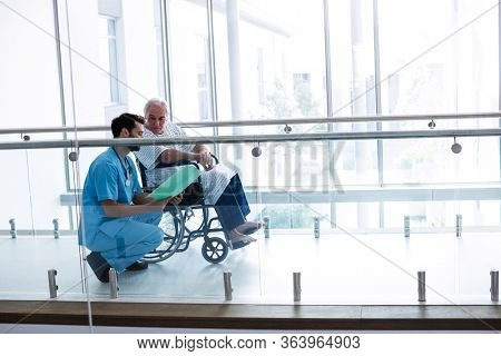 Doctor interacting with male senior patient in passageway at hospital