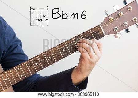Learn Guitar - Man In A Dark Blue Shirt Playing Guitar Chords Displayed On Whiteboard, Chord B Flat