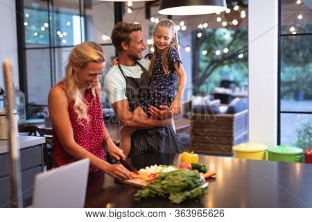 Caucasian family enjoying their time at home together, standing in a kitchen, using a laptop, a woman is cutting vegetables, social distancing and self isolation in quarantine lockdown during