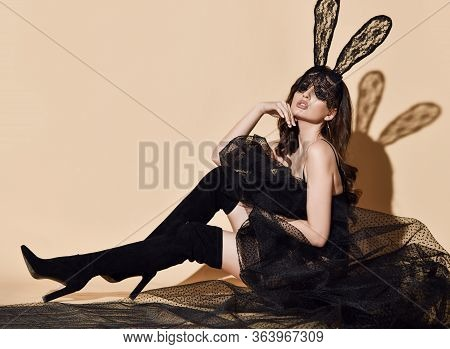 Young Beautiful Brunette Woman In Black High Boots, Sexy Transparent Cloth And Lace Rabbit Ears And