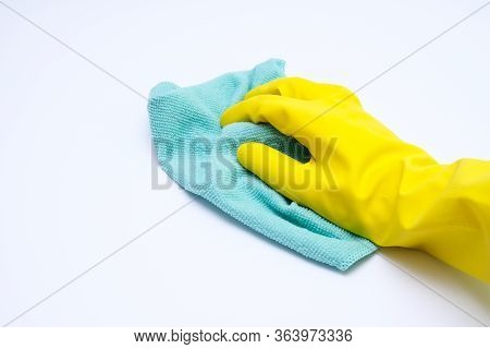 Hand In Yellow Rubber Glove Wiping Dust With Microfiber Cloth, Cleaning Up The House Concept, White