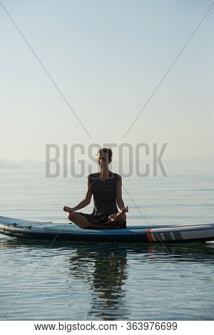 Young Woman Meditating Sitting In Lotus Position On Sup Board Floating On Calm Morning Sea Water.