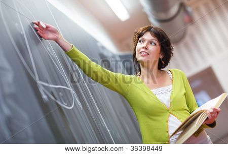 Pretty young elementary school/college teacher writing on the chalkboard/blackboard during a math class (color toned image; shallow DOF)