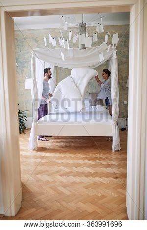 Young couple in love making the bed together and having fun.