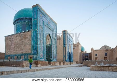 Woman tourist stands near the ancient building in the city of Samarkand in Uzbekistan at sunrise