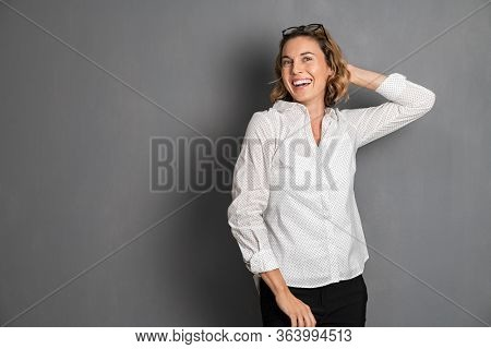 Portrait of excited middle aged woman smiling against grey background and looking at camera. Cheerful young businesswoman in formal. Beautiful german girl posing and dancing for camera with big grin.