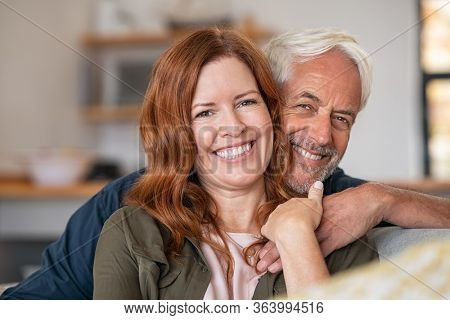 Portrait of middle aged couple hugging and looking at camera. Close up face of happy mature couple having fun at home. Senior man embracing his beautiful wife on the couch.