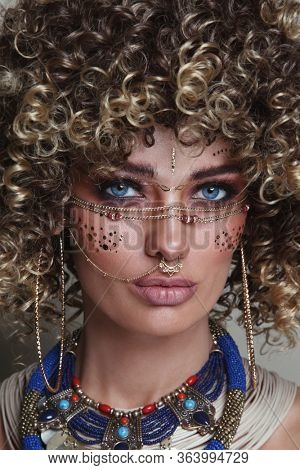 Close-up portrait of young beautiful woman with afro hair and fancy ethnic makeup